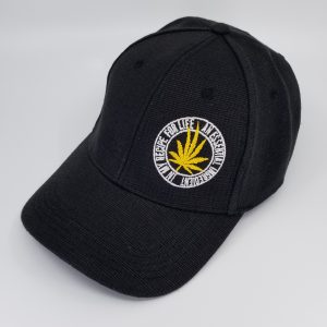 "Black Hemp Baseball-Style Hat with Yellow Cannabis Leaf and the text ""An Essential Ingredient in My Recipe for Life"""